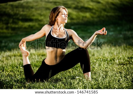 Young woman practicing yoga in a park on the grass - stock photo