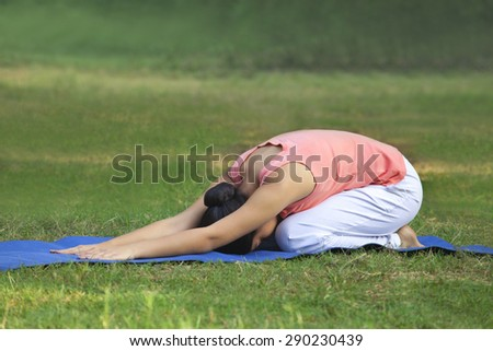 Young woman practicing yoga in lawn - stock photo