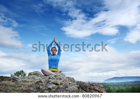 Young woman practicing yoga in lotus pose on top of mountain under blue sky. - stock photo