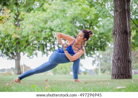 Young woman practicing yoga in the park on the green grass with fallen leaves in autumn with blurred background. Shallow depth of field