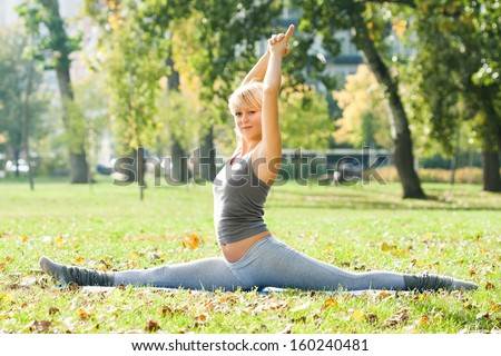 Young woman practicing yoga in the park,Yoga - Hanumanasana/Monkey Pose