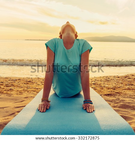 Young woman practicing yoga in upward facing dog pose on beach near the sea on sunset, front view - stock photo