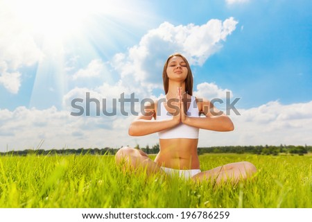 Young woman practicing yoga meditating outdoors in nature - stock photo