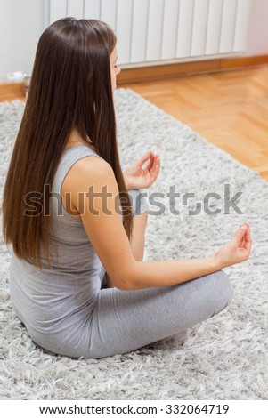 Young woman practicing yoga meditation at home. Fit caucasian female in sportswear exercising.Healthy lifestyle. - stock photo