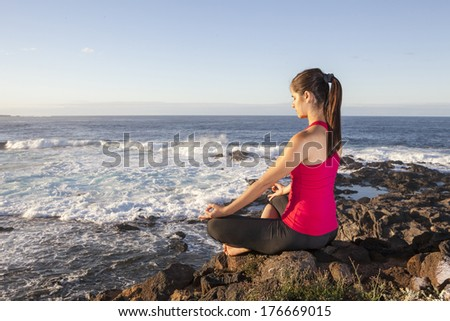 young woman practicing yoga meditation on the beach - stock photo