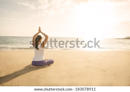 young woman practicing yoga meditation on the beach at sunset - stock photo
