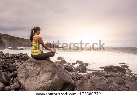 young woman practicing yoga meditation on the beach at sunset, lotus position - stock photo