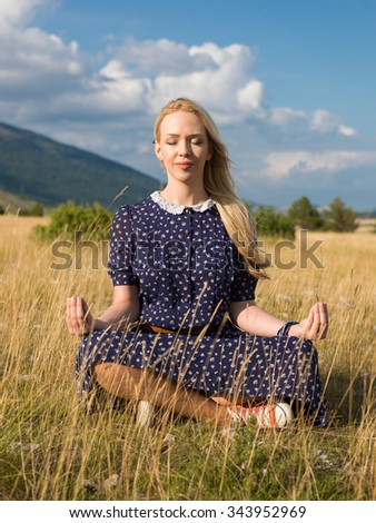 Young woman practicing yoga nature - stock photo