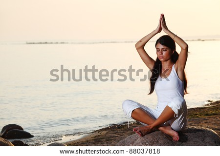 Young woman practicing yoga  near the ocean - stock photo