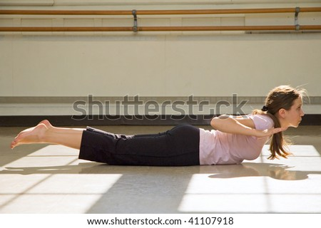 Young woman practicing yoga on floor. - stock photo