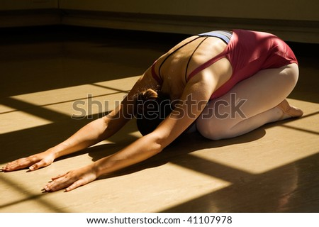 Young woman practicing yoga on floor.