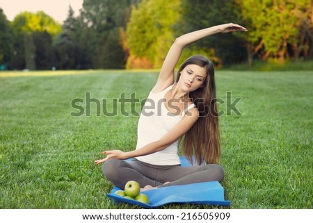 young woman practicing yoga on mat . Outdoors. healthy food. - stock photo