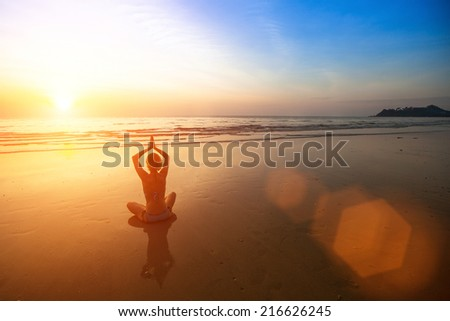 Young woman practicing yoga on sea beach during wonderful sunset.