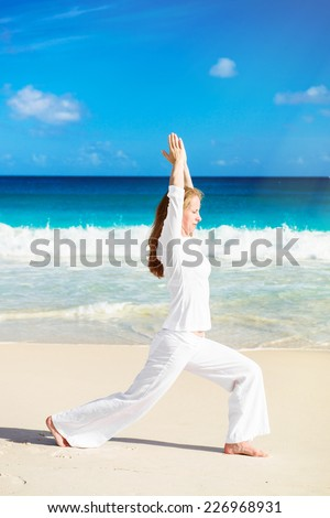 Young woman practicing yoga on the beach - stock photo