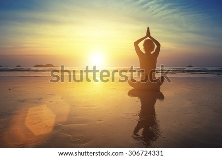 Young woman practicing yoga on the beach at amazing sunset (with reflection) - stock photo
