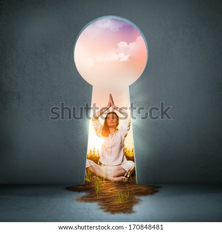 Young woman practicing yoga on the beach at sunset behind the keyhole - stock photo