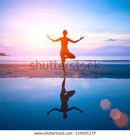 Young woman practicing yoga on the beach at sunset with reflection in water. - stock photo