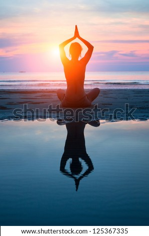 Young woman practicing yoga on the beach at sunset (with reflection in water) - stock photo