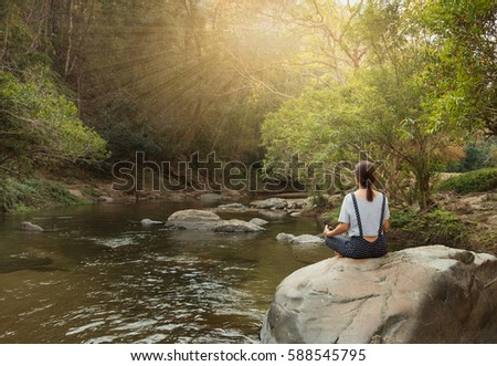 young woman practicing yoga on the rock in a stream at the morning