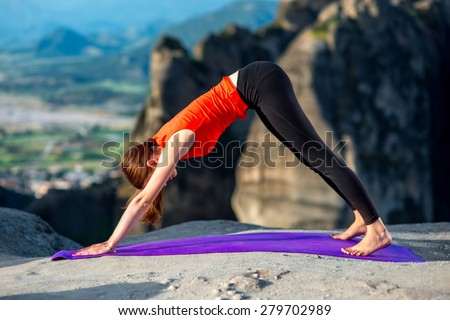 Young woman practicing yoga on the top of mountain