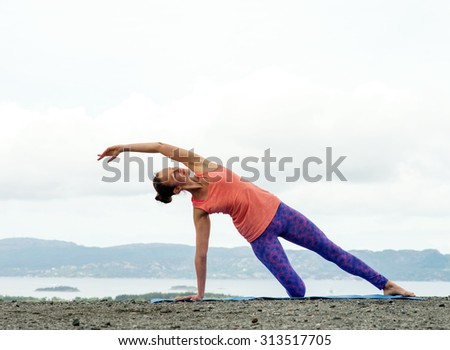 Young woman practicing yoga on top of a mountain