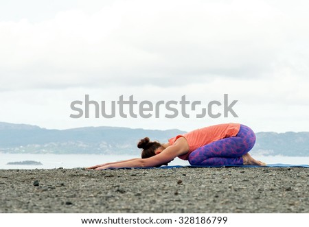 Young woman practicing yoga on top of a mountain - child's pose - stock photo
