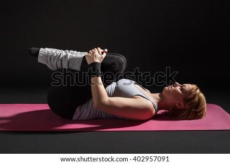 Young woman practicing yoga, Pawanmuktasana / Wind Relieving pose - stock photo