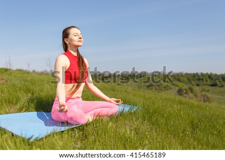 Young woman practicing yoga poses at outdoor. Girl doing perfect pose