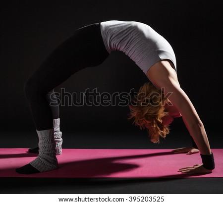 Young woman practicing yoga, Setuasana / Bridge pose - stock photo
