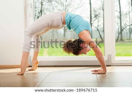 Young woman practicing yoga - Urdhva Dhanurasana / Upward bow pose indoor in front of the window - stock photo