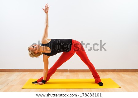 Young woman practicing yoga,Yoga-Virabhadrasana /Rotated warrior pose - stock photo