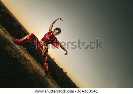 Young Woman Practising Wushu at Sunset - stock photo