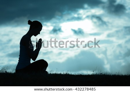 Young woman praying. - stock photo