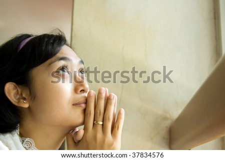 Young woman praying in church - stock photo