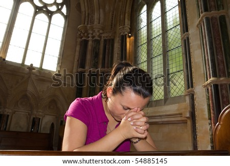 Young woman praying in the church - stock photo