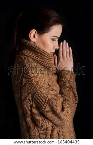 Young woman praying. Over black background. - stock photo
