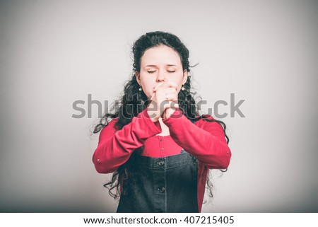 young woman praying, religion concept, dressed in a overalls, close-up isolated on a gray background - stock photo