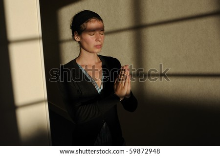 Young woman praying with closed eyes in little church. - stock photo