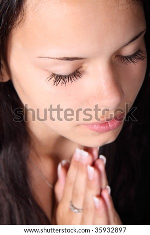young woman praying with her eyes closed - stock photo