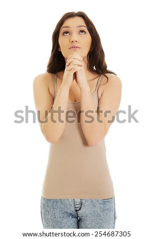 Young woman praying with her hands together and looking up. - stock photo