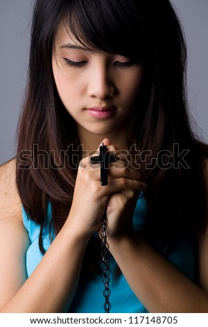 Young woman  praying with rosary in hand - stock photo