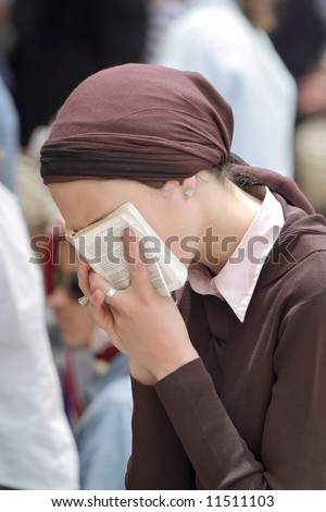 Young woman prays in the wailing wall in Jerusalem. - stock photo
