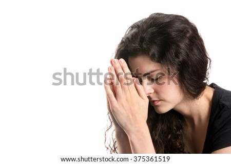 Young woman prays with head bowed and hands together. - stock photo