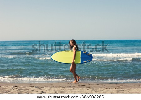 young woman prepare for surf on board full body shot on sandy beach by the sea - stock photo