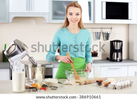 Young woman preparing dough in a bowl
