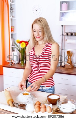 Young woman preparing dough in the kitchen - stock photo