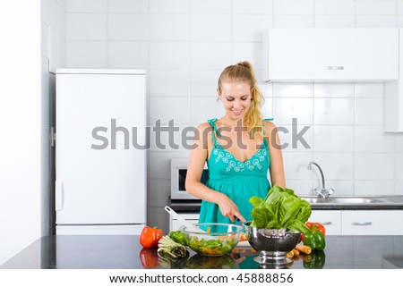 young woman preparing food in kitchen - stock photo