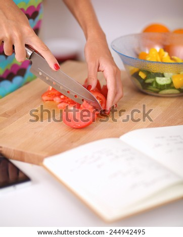 Young woman preparing salad in the kitchen - stock photo