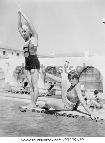 Young woman preparing to dive from a diving platform with another woman sitting beside her - stock photo
