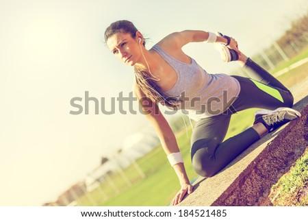Young woman preparing to run - stock photo